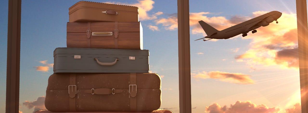 Una pila di valigie con un aereo in partenza sullo sfondo al tramonto