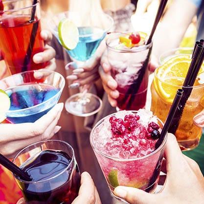 Bicchieri di cocktail estivi e colorati decorati con bacchette e frutta