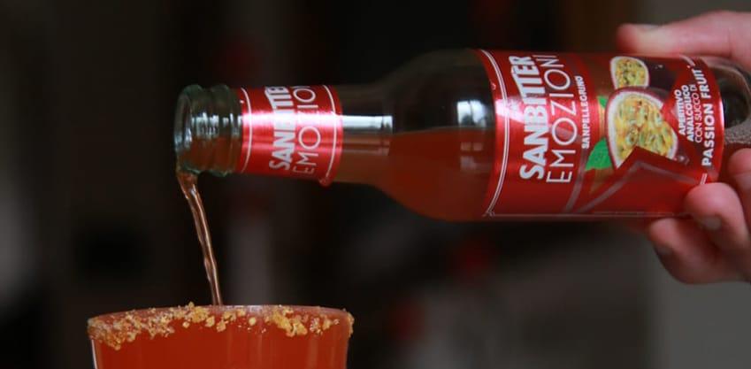 Un bicchiere di cocktail rosso con emozioni sanbitter