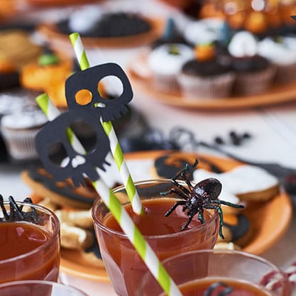 cocktail di Halloween decorato con ragni e cannucce sormontate da teschi