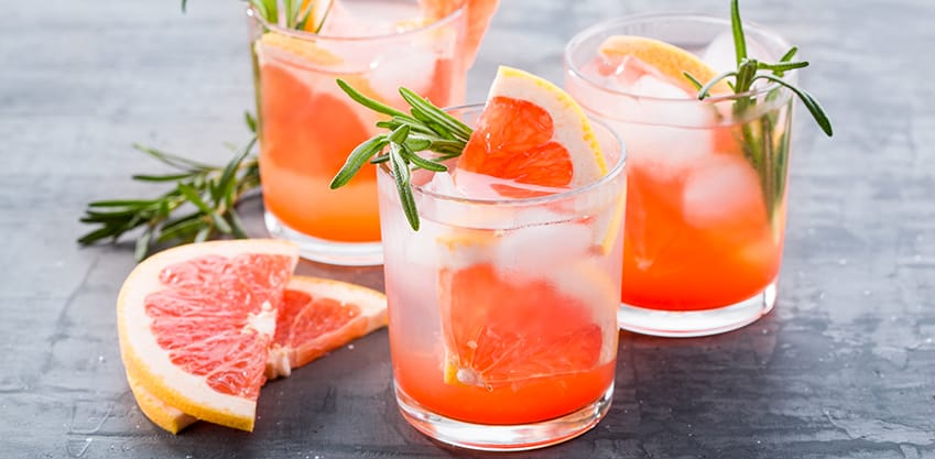 3 bicchieri di succo di pompelmo con foglie di rosmarino