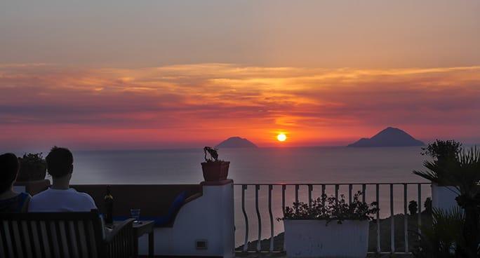 Una coppia osserva il tramonto sul mare a Lipari