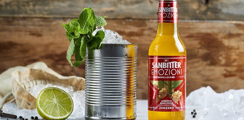 Bottiglia di Sanbitter con estratto di zenzero e barattolo con ghiaccio, menta, limone e spezie