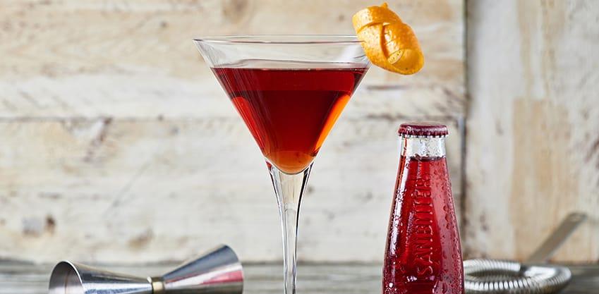 Cocktail rosso con una bottiglietta di Sanbittèr accanto
