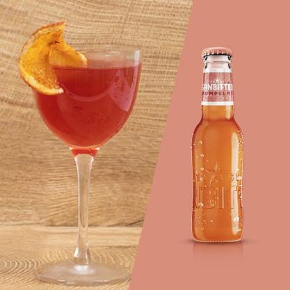 Cocktail rosso grapefruit bitter con vicino una bottiglie di Sanbittèr Emozioni Pompelmo
