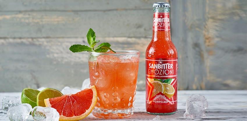 Bottiglia Sanbittèr al succo di pompelmo e bicchiere con cocktail pompelmo, menta, lime e ghiaccio