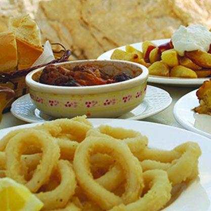 Aperitivo spagnolo accompagnato da tapas, polpo e anelli di calamari fritti